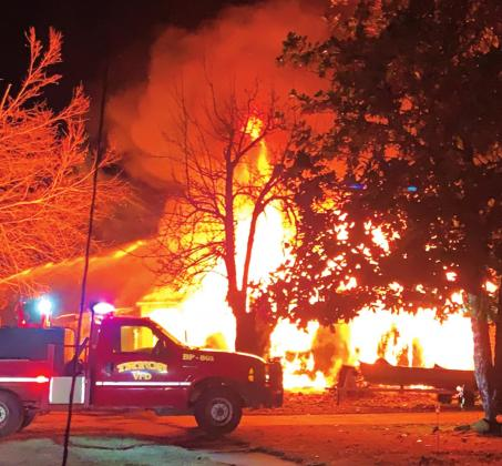 Firefighters battle a blaze in Tryon that involved two houses and an out building Monday.